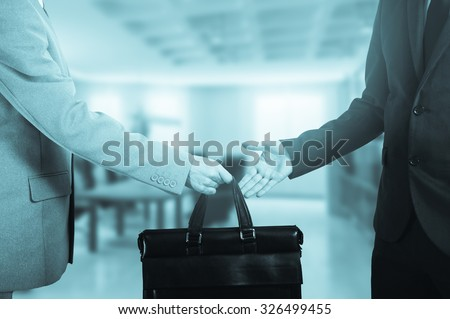 business transfer. handover of a suitcase in the hands of partners.