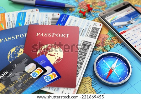Business travel and tourism concept: air tickets or boarding pass, passports, smartphone with online airline tickets booking or reservation internet app, compass, credit cards and pen on world map - stock photo