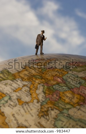 Business travel figure on globe, above europe, with clouds in background - stock photo