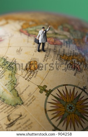Business travel figure on globe with green background - stock photo