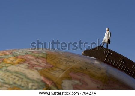 Business travel figure on globe with light blue background - stock photo