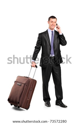 Business traveler carrying a suitcase and talking on a cell phone isolated on white background - stock photo