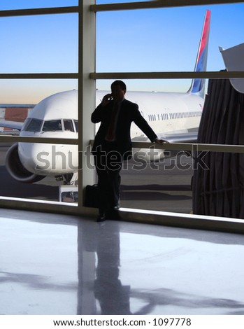 Business traveler makes a call while waiting for his flight - stock photo