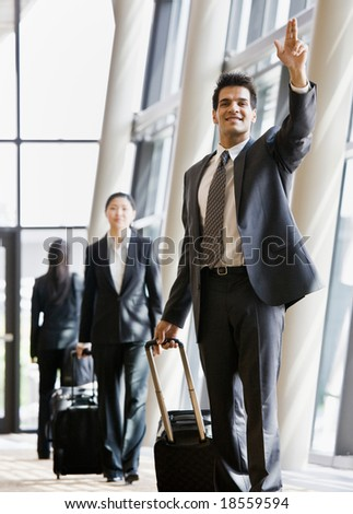 Business traveler pulling suitcase and gesturing to co-worker - stock photo