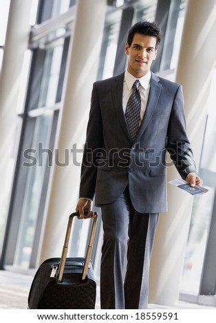 Business traveler pulling suitcase and holding passport and airline ticket - stock photo