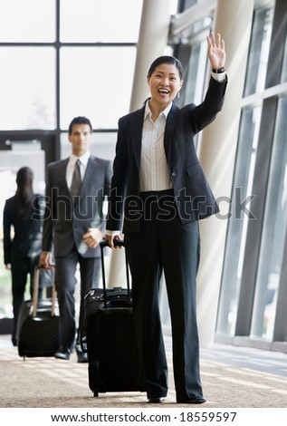 Business traveler pulling suitcase and waving to co-worker - stock photo