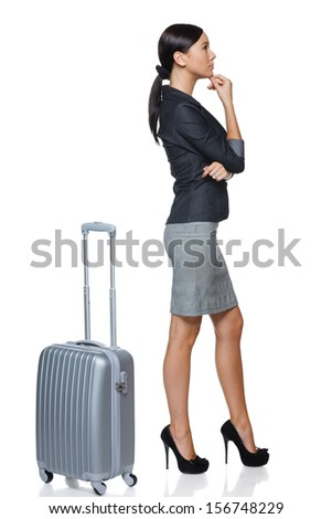 Business traveler. Side view of  pensive woman in full length with suitcase, over white background - stock photo