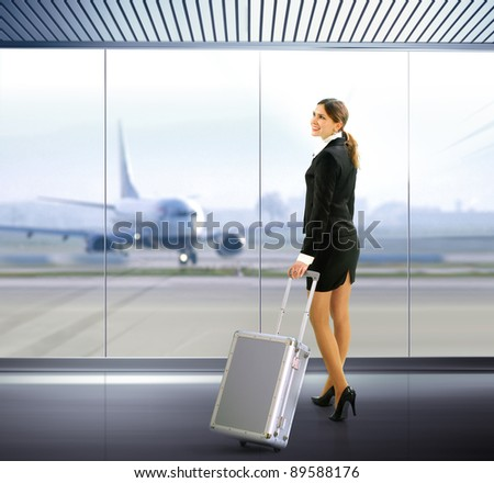 Business traveler with luggage in airport - stock photo