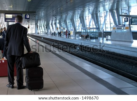 Business Trip. A businessman is waiting for the train on a modern trainstation. - stock photo
