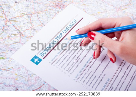 Business trip check list, woman holding blue pencil - stock photo