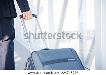 Business trip. Close-up of businessman carrying suitcase while walking through a passenger boarding bridge - stock photo