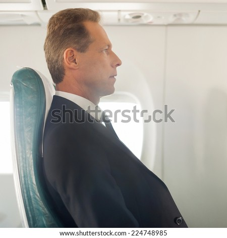 Business trip. Side view of confident mature businessman sitting at his seat in airplane  - stock photo