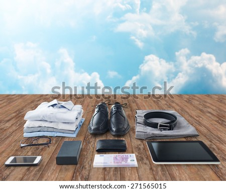 business trip, style, clothes and objects concept - close up of formal male clothes and personal stuff on wooden floor over blue sky with clouds background