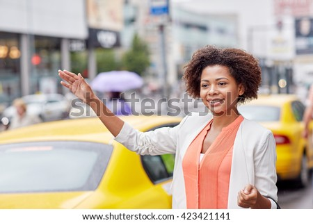 business trip, transportation and people concept - young smiling african american woman catching taxi at city street - stock photo