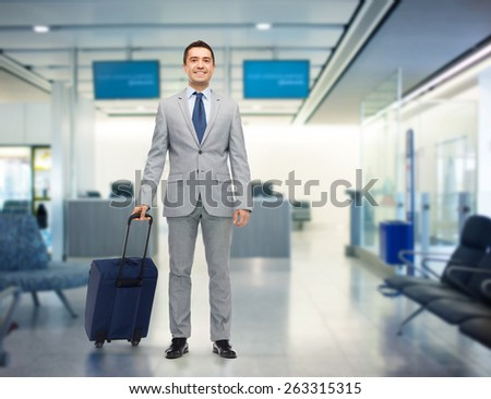 business trip, traveling, luggage and people concept - happy businessman in suit with travel bag over airport background - stock photo