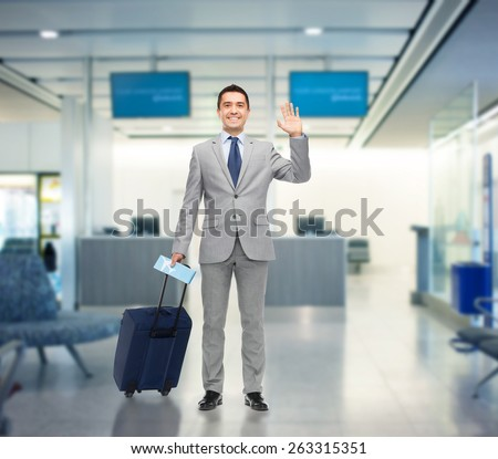 business trip, traveling, luggage and people concept - happy businessman in suit with travel bag and air ticket waving hand over airport background - stock photo