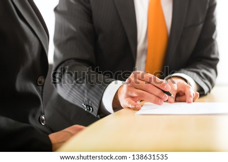 Business - Two businesspeople or professionals have a conversation in an office - stock photo