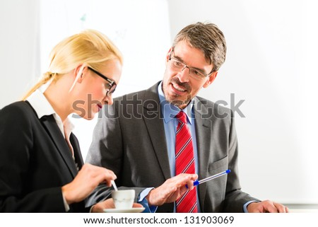 Business - Two businesspeople or professionals have a conversation in an office and drinking coffee or espresso - stock photo