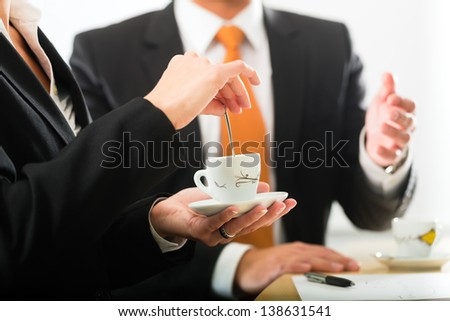 Business - Two businesspeople or professionals have a conversation in an office drinking coffee or espresso - stock photo