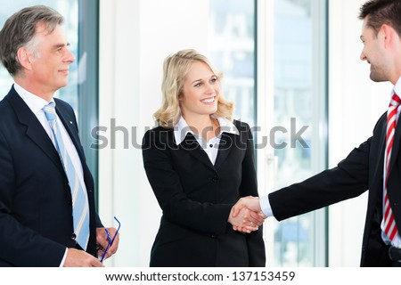 Business - Two businesspeople shaking hands - stock photo