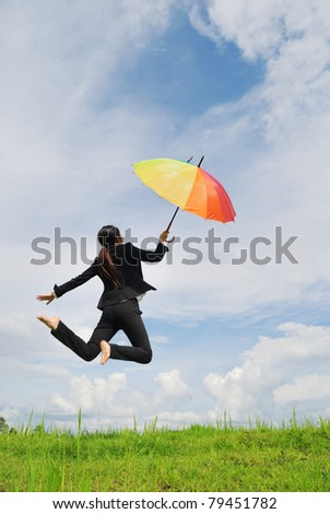 Business umbrella woman jumping to blue sky in grassland with rainbow umbrella - stock photo