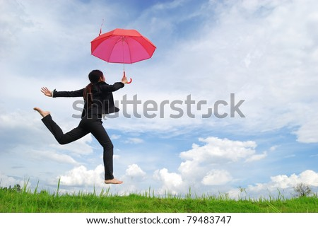 Business umbrella woman jumping to blue sky in grassland with red umbrella - stock photo