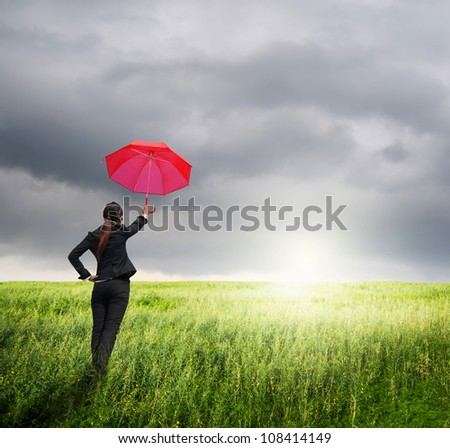 Business umbrella woman standing to rainclouds in grassland with red umbrella - stock photo