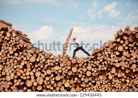 business vision -hardworking  businessman  on top of large pile of cut wooden logs - stock photo