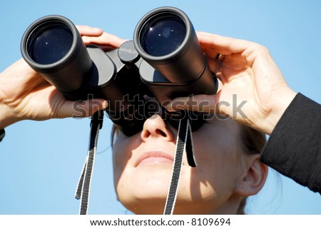 business vision - woman with binoculars looking at the sky
