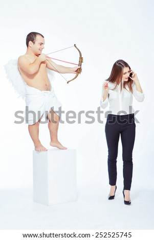 Business vs love. Portrait of an adorable little cupid with a bow taking in sight a young beautiful businesswoman taking over the cell phone isolated on white with copy space - stock photo