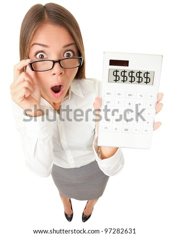 Business woman accountant shocked showing dollar signs on calculator. Surplus, debt or financial crisis concept image. Funny surprised young woman isolated on white background in high angle view. - stock photo