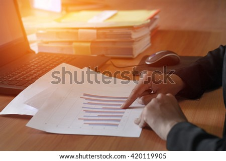 business woman analyzes the charts on the desk - stock photo