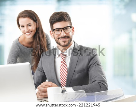 Business woman and business man working together on laptop while sitting at office.  - stock photo