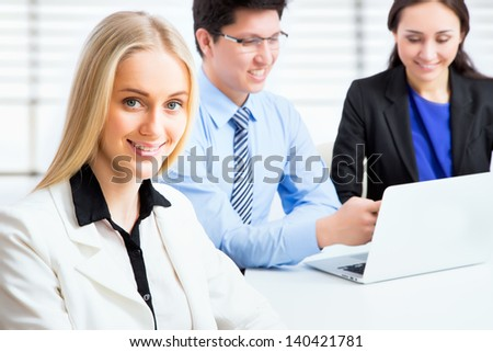 Business woman and her collegues working together in an office - stock photo
