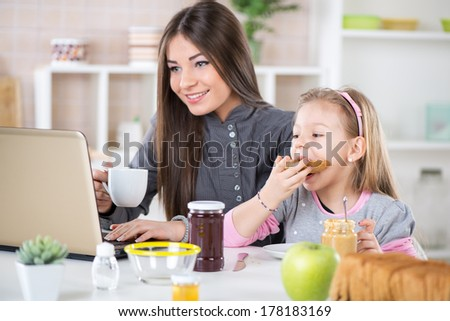 Business Woman and her daughter breakfast in the kitchen. Little girl eats bread with peanut butter. Beautiful young Business woman drinking coffee and reading mail before going to work. - stock photo