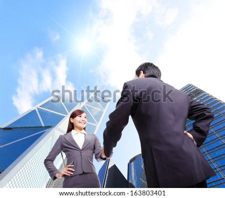 Business woman and man handshake with business office building background, asian, hong kong - stock photo