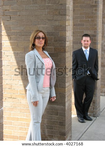 Business woman and man standing against a brick wall