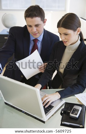 Business woman and man working at a laptop computer - stock photo