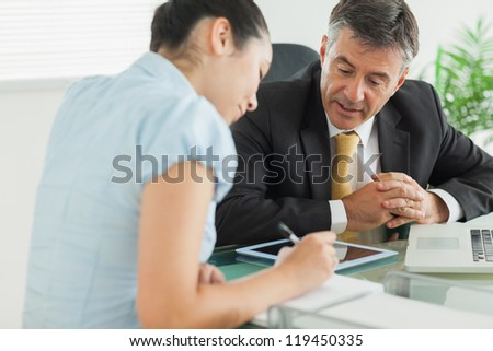 Business woman and man working at table with notepad and laptop in an office - stock photo