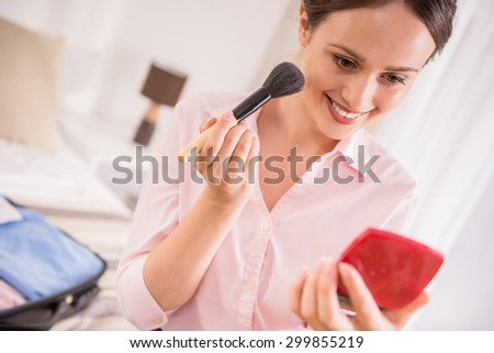 Business woman applying make-up while sitting on bed at the hotel room. - stock photo