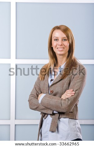 Business woman arms crossed in a modern office - stock photo