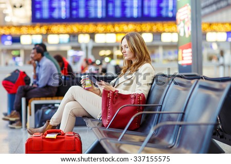 Business woman at international airport reading book and drinking coffee in terminal. Angry passenger waiting. Canceled flight due to pilot strike. - stock photo