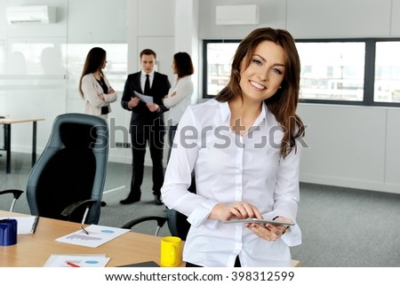 Business woman at modern office with people group in a background.  - stock photo
