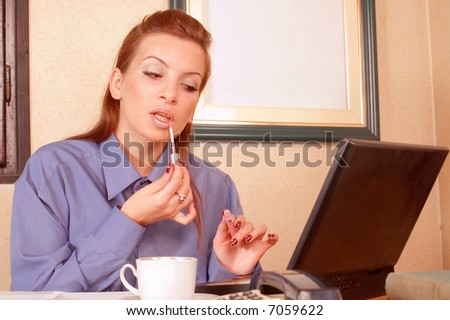 Business woman at office applying make up