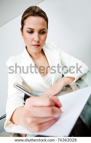 Business woman at the office sitting on her desk writing