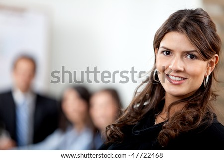 Business woman at the office with a group behind