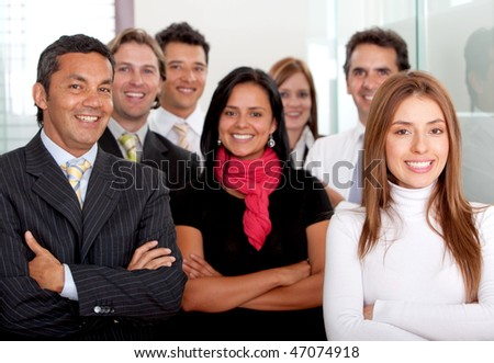 Business woman at the office with a group behind her - stock photo