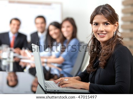 Business woman at the office with a laptop smiling