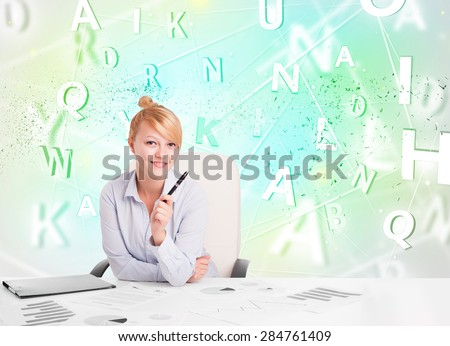 Business woman at white desk with green word cloud - stock photo