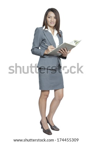 Business woman attractive young pretty in office standing enjoy using a pen writing diary note book smiling positive  on white background